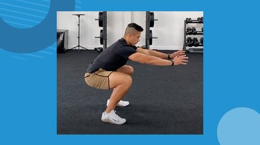 trainer showing correct air squat form in the gym