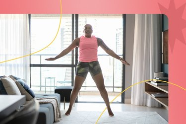 Woman doing jumping jacks as a warm-up before a leg workout in her living room