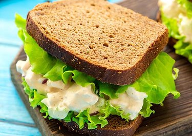 The Best Classic Chicken Salad with whole grain bread and green lettuce on a wood slab