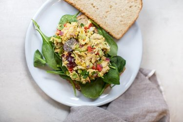 Curry Chicken Salad with a slice of whole grain bread on a bed of greens and white plate