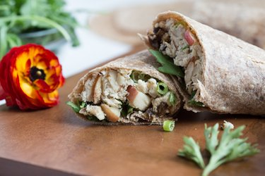 Waldorf Chicken Salad Wrap with a sprig of arugula and red flower on a wooden slab