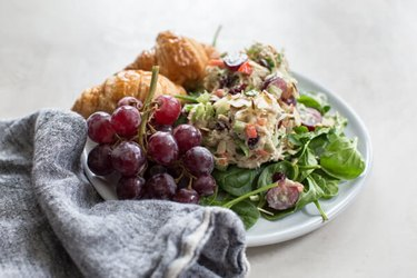 Greek Yogurt Chicken Salad With Grapes and croissants on a white plate with a gray cloth napkin