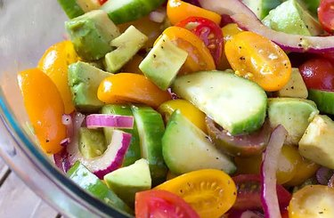 Avocado Cucumber Tomato Salad With Balsamic Vinaigrette with yellow tomatoes in a clear bowl
