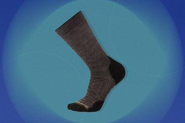 grey smartwool outdoor light crew socks on a blue-green background