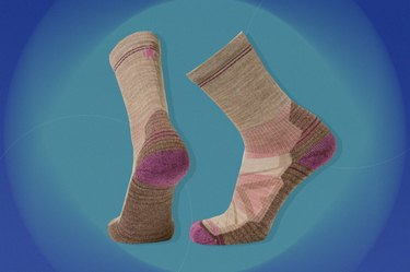 grey and pink smartwool performance hike light-cushion crew socks on a blue-green background
