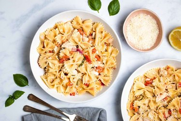 Bowtie pasta with tomato and diced chicken on a white plate.
