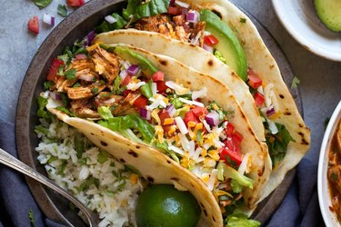 Two chicken tacos in flour tortillas topped with chopped red onion, tomato, avocado and cheese on a brown plate on gray background.