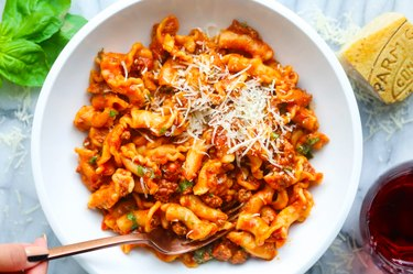 Pasta with ground beef in tomato sauce on a white plate on marble background