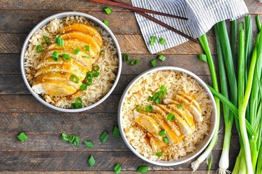 Two bowls of brown rice with sliced chicken drizzled in teriyaki sauce over wooden background.