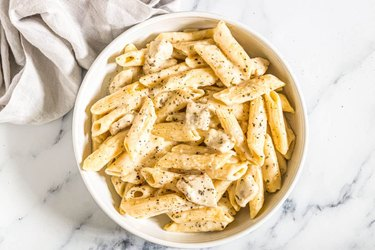 Penne pasta and diced chicken in a cheesy sauce topped with black pepper in a white bowl
