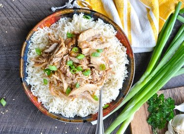 Colorful bowl of rice topped with chicken in a sesame garlic sauce with chopped green onions over wooden background.