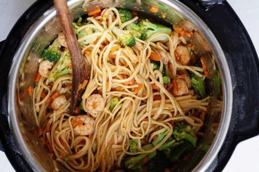 Instant Pot filled with lo mein noodles, broccoli, carrots, and shrimp.