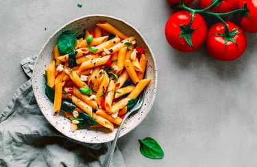 Penne pasta with spinach and diced tomatoes in a white speckled bowl on gray background.