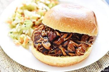 Burger bun with shredded teriyaki chicken alongside buttered vegetables on a white plate.