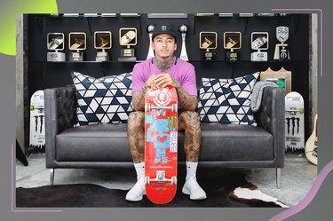 skateboard Nyjah Huston holding skateboard sitting on gray couch