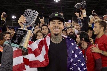 Nyjah Huston with skateboarding award and American flag