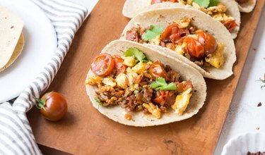 Skillet Breakfast Tacos With Chorizo And Sauteed Tomatoes with tortillas on a brown wooden cutting board
