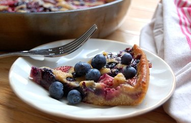 Skillet Berry Cobbler with blueberries on a white plate with a fork