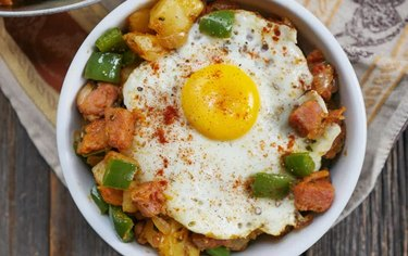 Spicy Ham and Potato Breakfast Hash Skillet with a fried egg in a white bowl