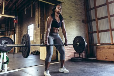 woman deadlifting barbell in industrial-looking gym