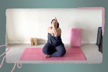 Woman doing seated eagle arms pose for yoga challenge