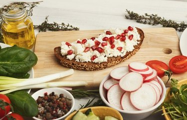Breakfast Recipes for Longevity Ricotta and Pomegranate Bruschetta on a wood cutting board with apple and tomato slices