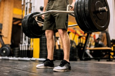 close-up shot of a man doing a trap bar deadlift in the gym