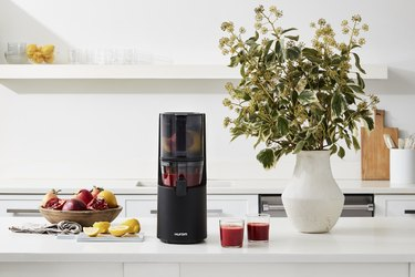 hurom juicer on counter with fruits and juice