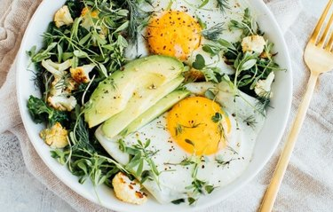 Egg and Greens Bowl (aka Breakfast Salad) in a white bowl with fried eggs, avocado slices and a fork
