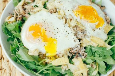 Sardine Breakfast Salad in a white bowl with peppered poached eggs