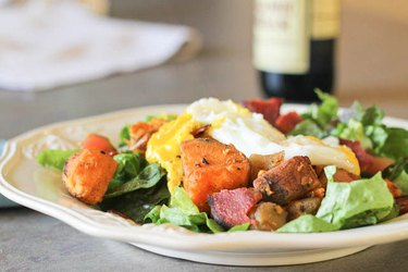 Warm Breakfast Salad on white plate with fried eggs and diced sweet potatoes
