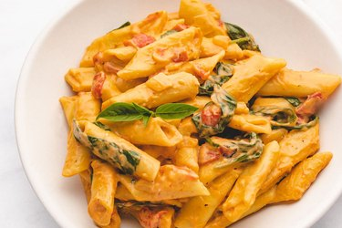 Instant pot penne pasta in creamy sauce on a white plate.