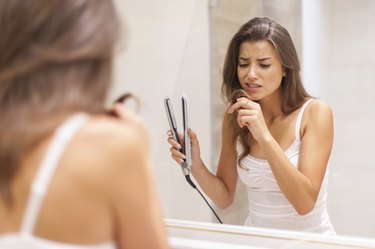 Woman straightening hair in bathroom