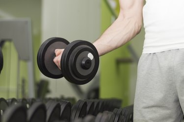 Unrecognizable person taking dumbbells in a gym