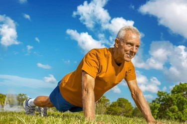 Determined senior man doing pushup exercise on meadow