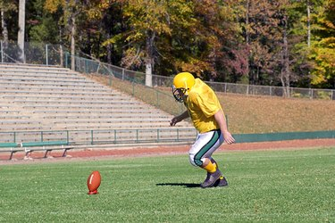 Football kicker practicing on field