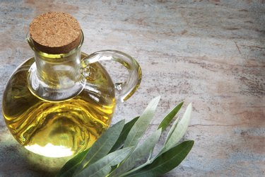 Olive Oil and Leaves on Rustic Timber