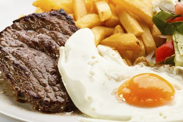 Beefsteak, fried egg, French fries and vegetables