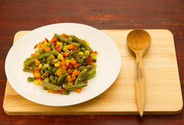 mixed vegetables on white plate on wooden background
