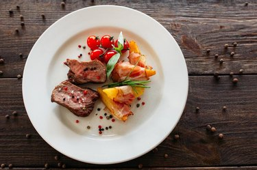 Medium rare pork steak with fresh vegetables. Food photography of pork steak with potatoes and tomatoes cherry. Tasty cook meat with vegetables on dark wooden background.