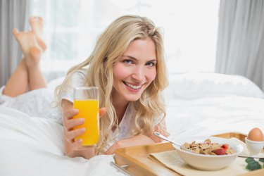 Happy young woman having breakfast in bed