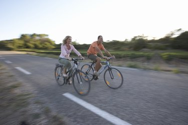 Woman and man riding bicycles on country road, focus on cyclists