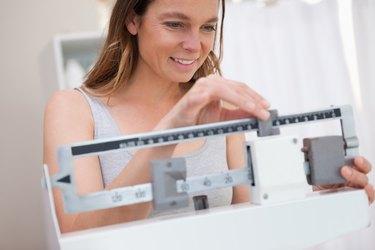 Woman adjusting medical scale