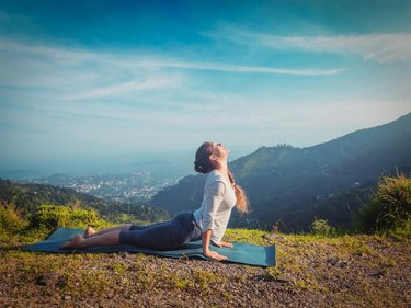 Yoga outdoors  - woman practices Ashtanga Vinyasa yoga Surya Namaskar Sun Salutation asana Urdhva Mukha Svanasana - upward facing dog pose in mountains in the morning. Vintage retro effect filtered hipster style image.
