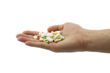 Man holding heap of different pills in the hand