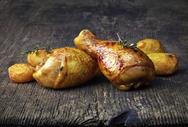 Roasted chicken legs and potatoes on wooden cutting board