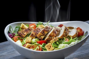 Hot chicken and fresh vegetables in healthy salad