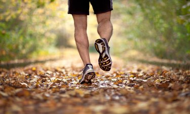 runner's lower legs on leafy trail