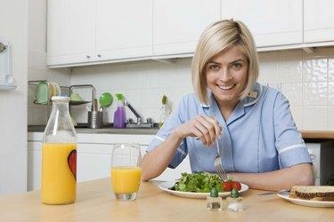 Woman eating salad with orange juice