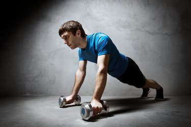 Man pushing up from the dumbbells on empty gray  wall backdrop